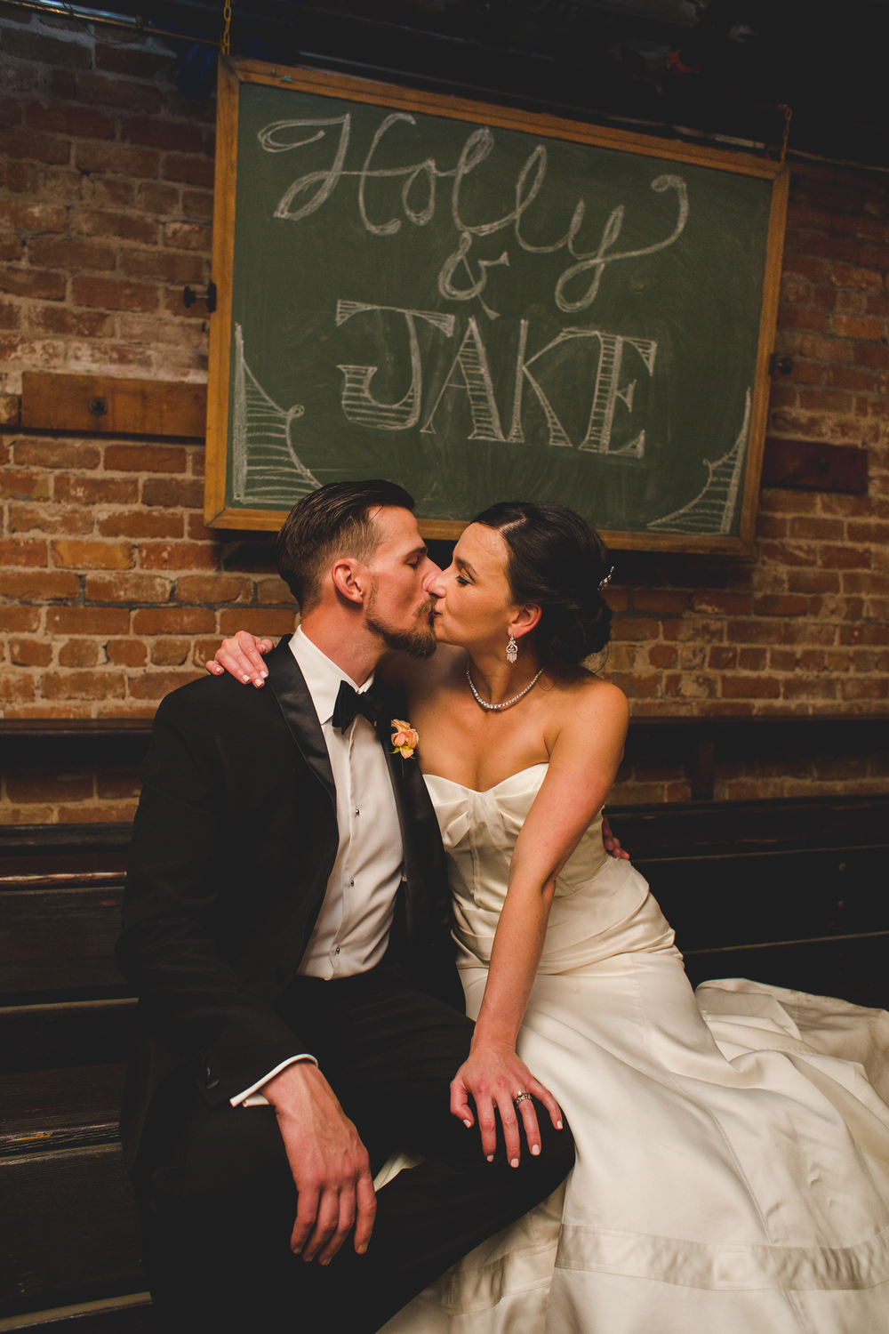 bride and groom under chalkboard sign the duce hj