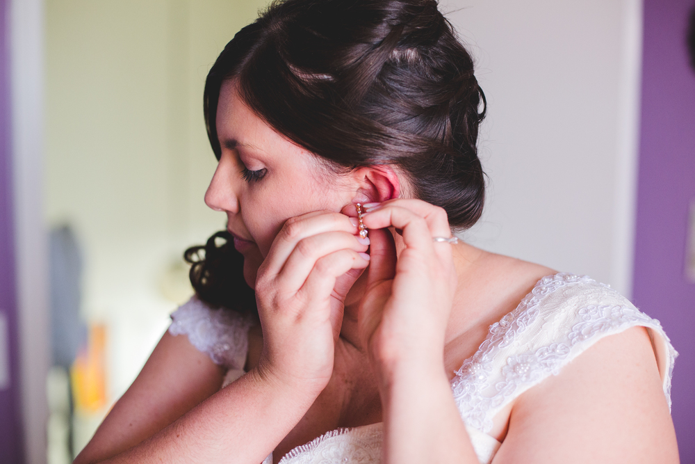 bride putting on earrings sd