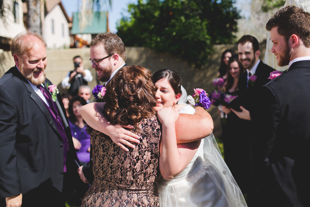 bride cries with groom's mother during ceremony sd