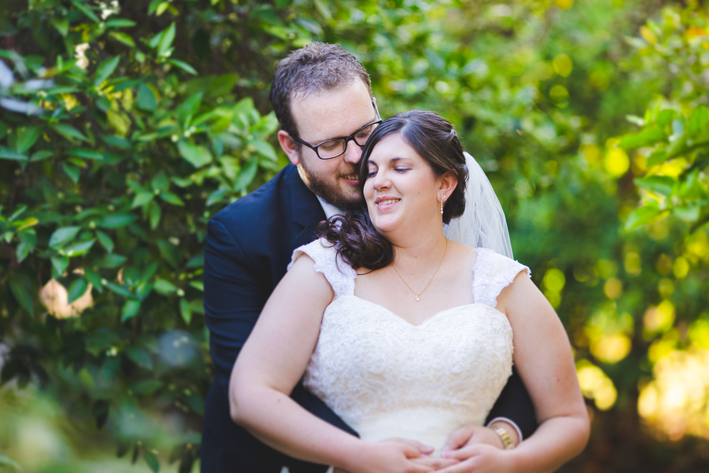 groom makes bride smile as he holds her sd