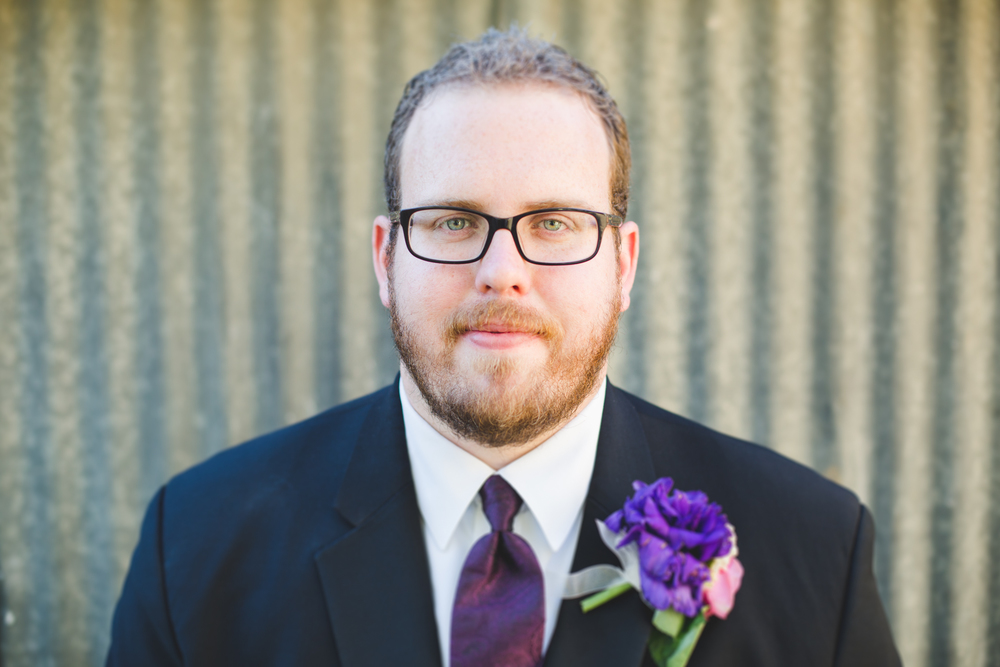 color portrait of groom in front of shed sd