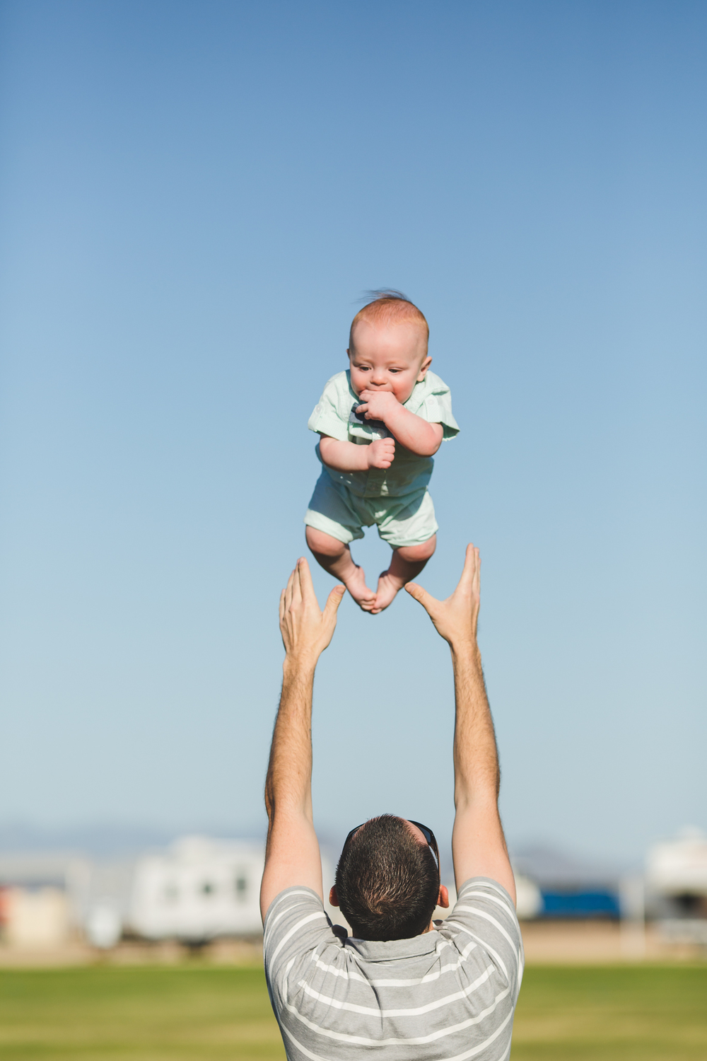 dad tosses baby son in the air cute