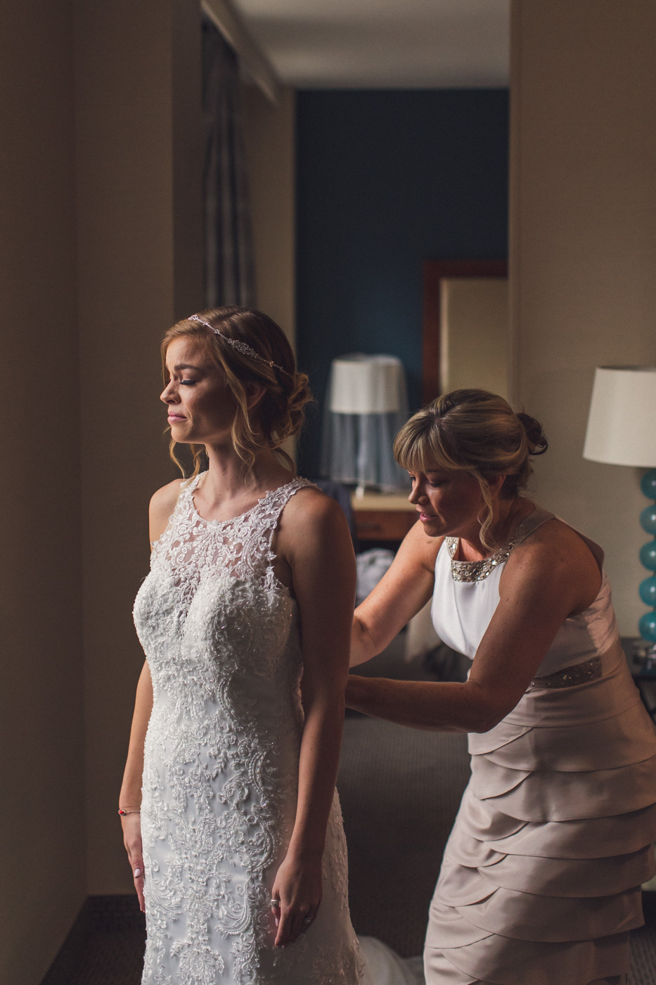 mother-getting-daughter-into-wedding-dress