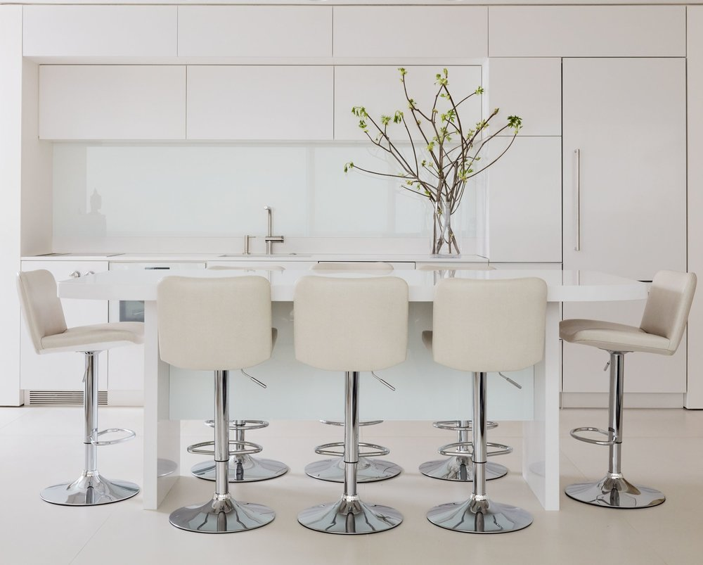 The sleek kitchen features cabinets and countertops made from Silestone in Zeus White Extreme. Custom-designed stools are covered in shagreen-imprinted leather from Jerry Pair's Cattlelac Collection in Barley
