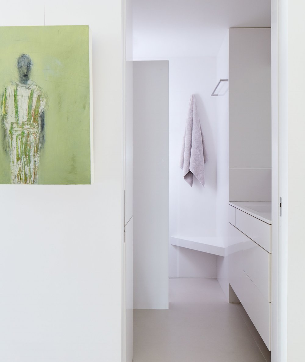 A painting by Marianne Kolb adds a burst of color to the all-white guest bathroom.