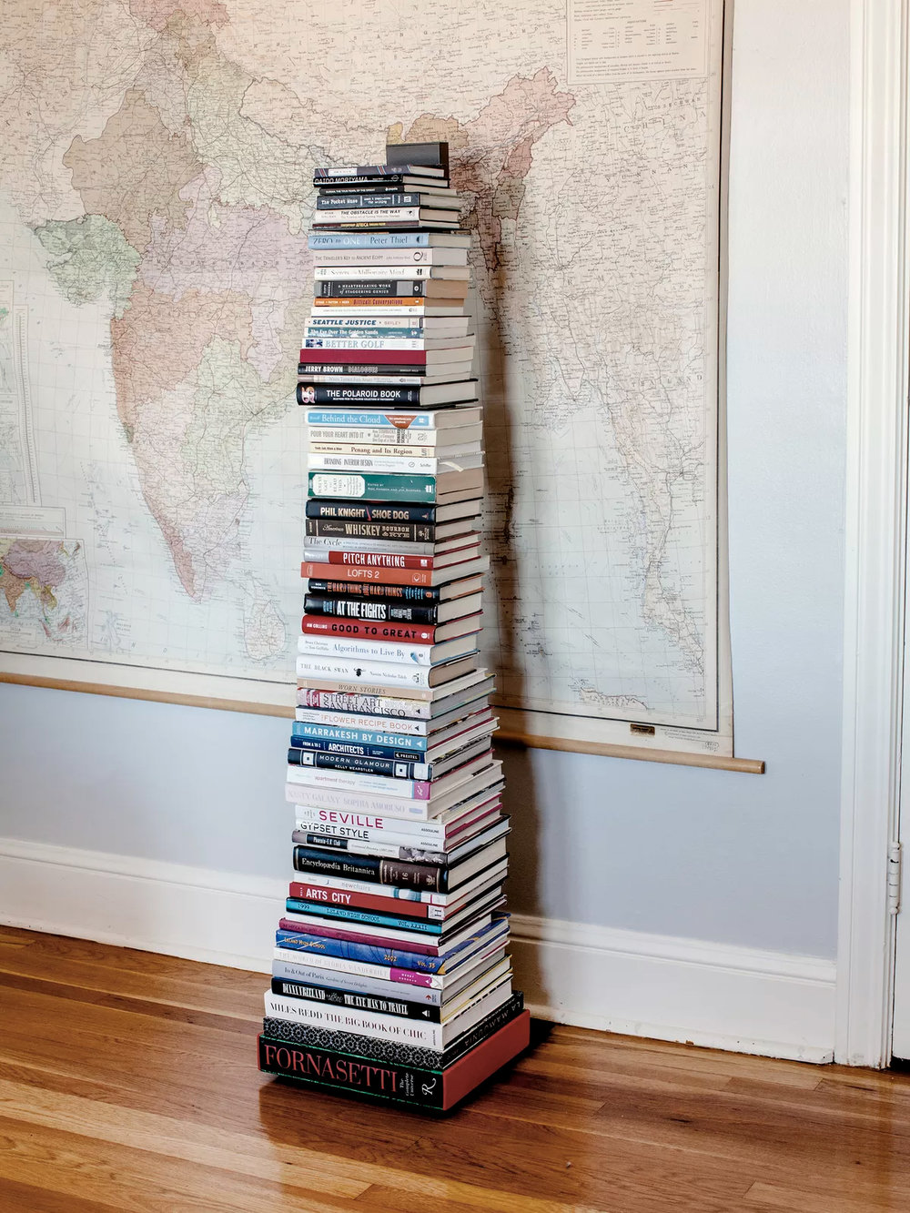 A vertical bookshelf stands in front of a vintage map.