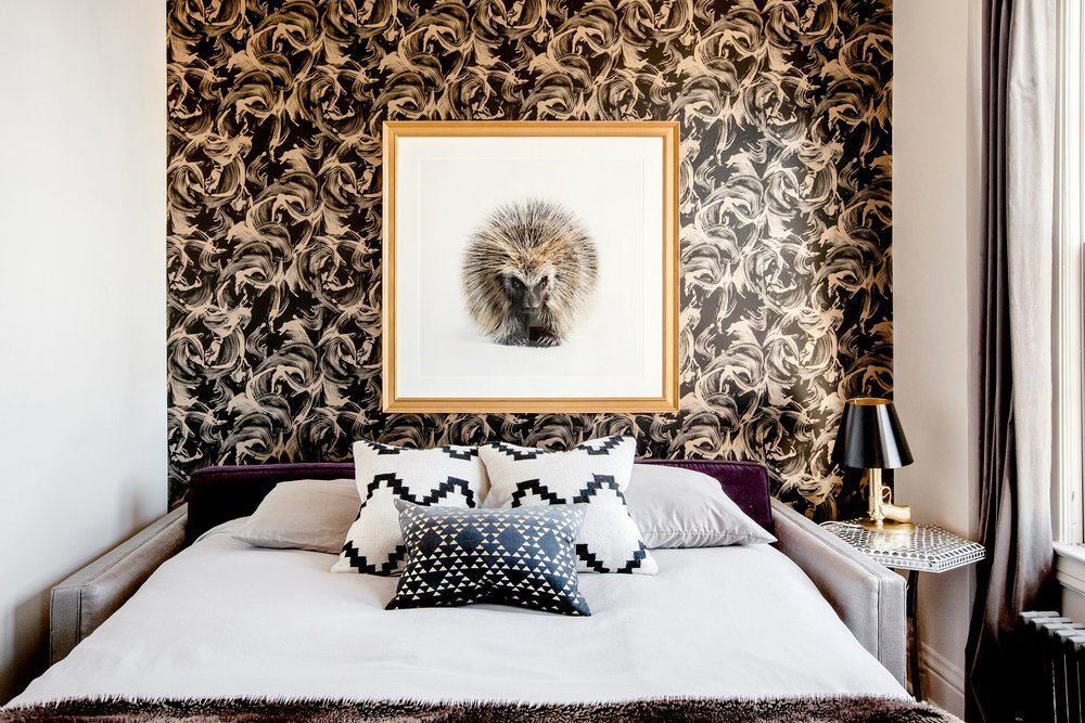 The  Mitchell Gold Bob Williams sofa  from Ruby Living unfolds to make a guest bed. The wallpaper is by  Tempaper , the art is by  Randal Ford , the bedside lamp is by Ken Fulk .