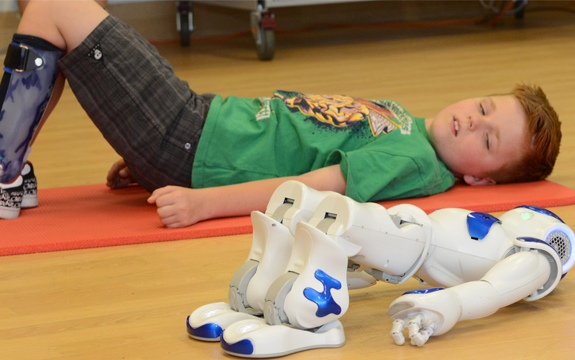 NAO and 9-year-old Miles working on 'bridge' exercises together.