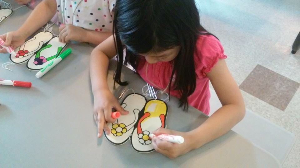 The Anchor Christian Church in Bensenville volunteering at Kids Camp girl coloring sandals art at Camp LRCA in Crown Point, Indiana