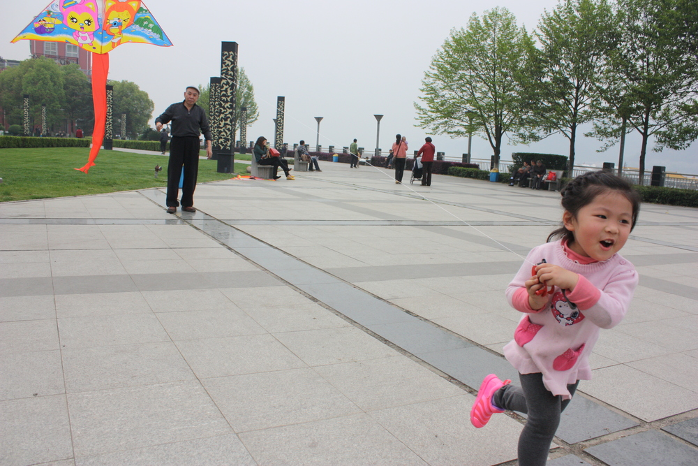 Girl and Grandfather Fly a Kite