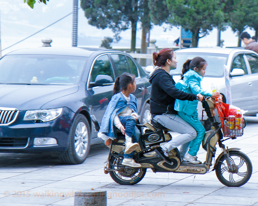 I never get used to seeing three, four, or sometimes five people on a motor bike. Helmets haven't really caught on yet here. They look careful though.  It is the ones who are smoking, not wearing a helmet and talking on their cell phones who are the ones to worry about.