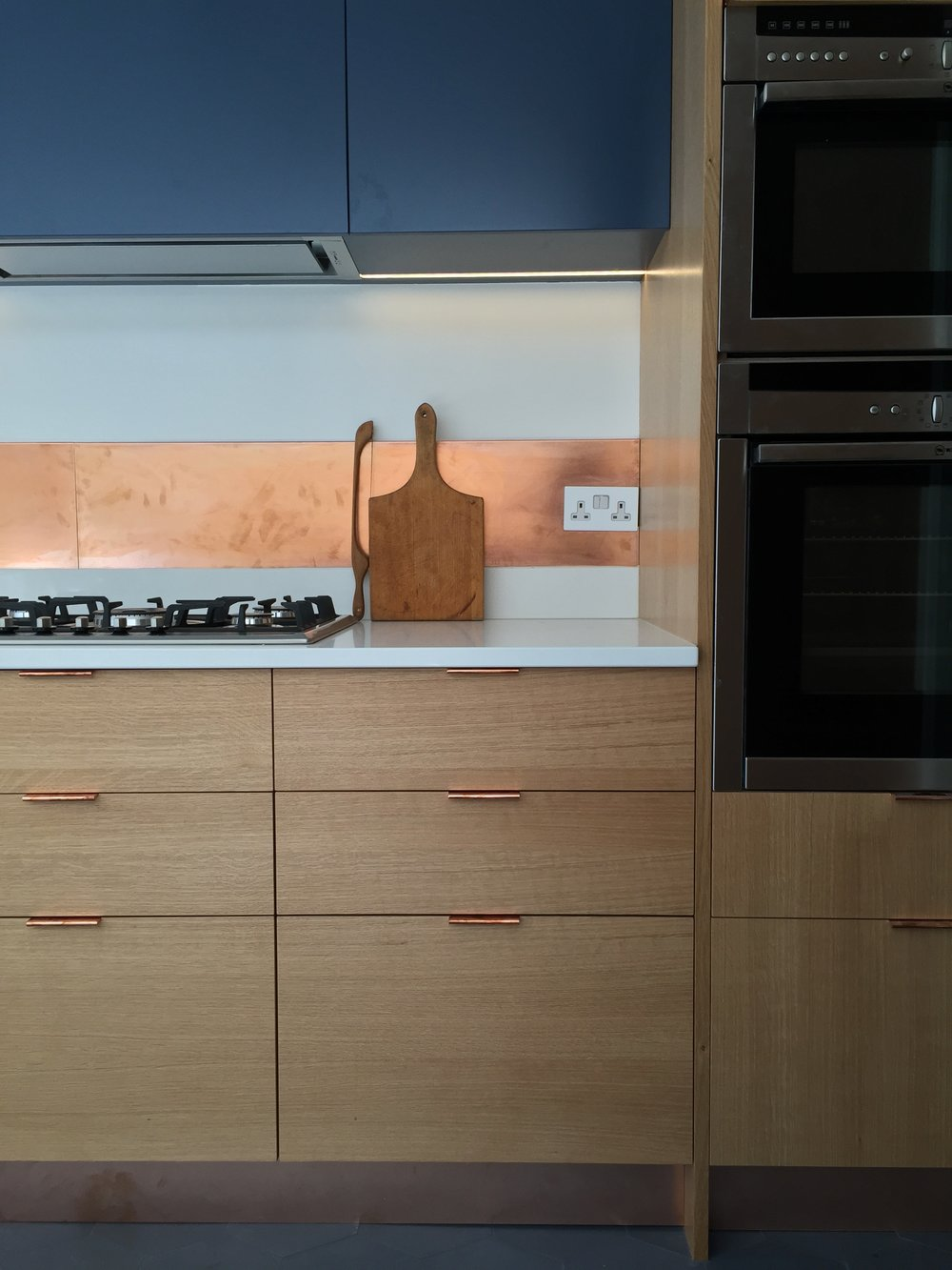 Kitchen cabinets with cooper detailing and handles