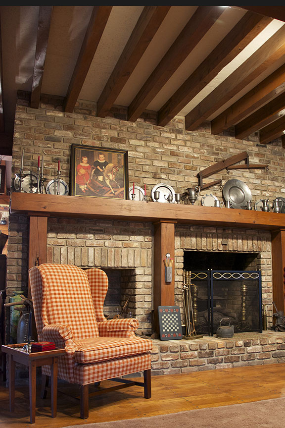 Reclaimed Antique Heart Pine beams in a residential ceiling. A reclaimed beam mantel atop a fireplace of reclaimed antique bricks.