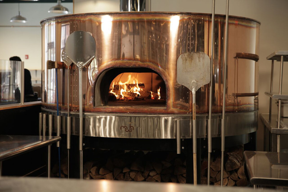 Jack's Abby has fire roasted pizza, made to order in this Maine Wood Heat copper open fire oven