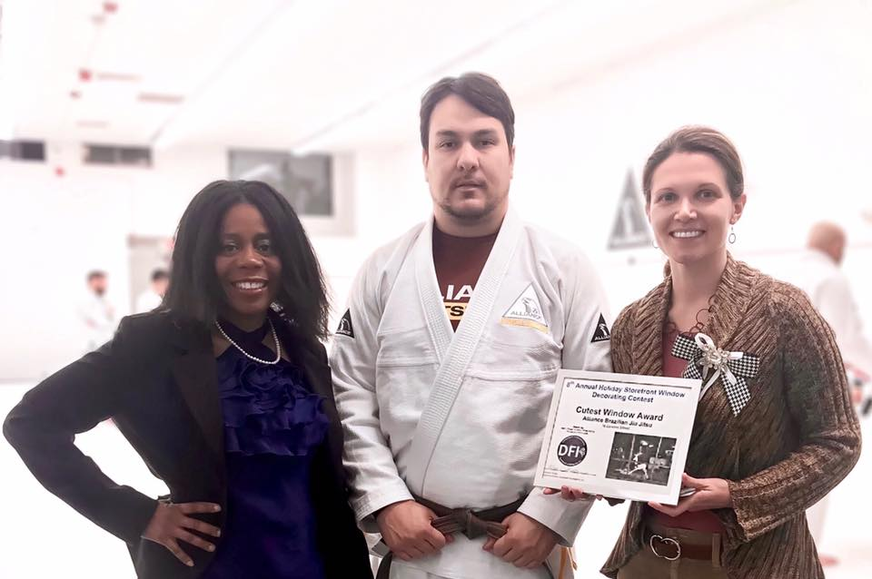 The  Cutest Storefront Award  was presented by Hoops and Homework Board Director Leslie White Harvey (left) to Samuel Almeida, owner of  Alliance Jiu Jitsu Framingham .