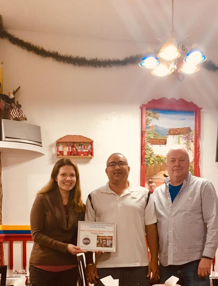 David Blais (right), Director of Daniel's Table and Co-owner Foodie Cafe, presents the  Most Traditional Storefront Award  to Ignacio Jaramillo (center), co-owner of  Pueblito Paisa .