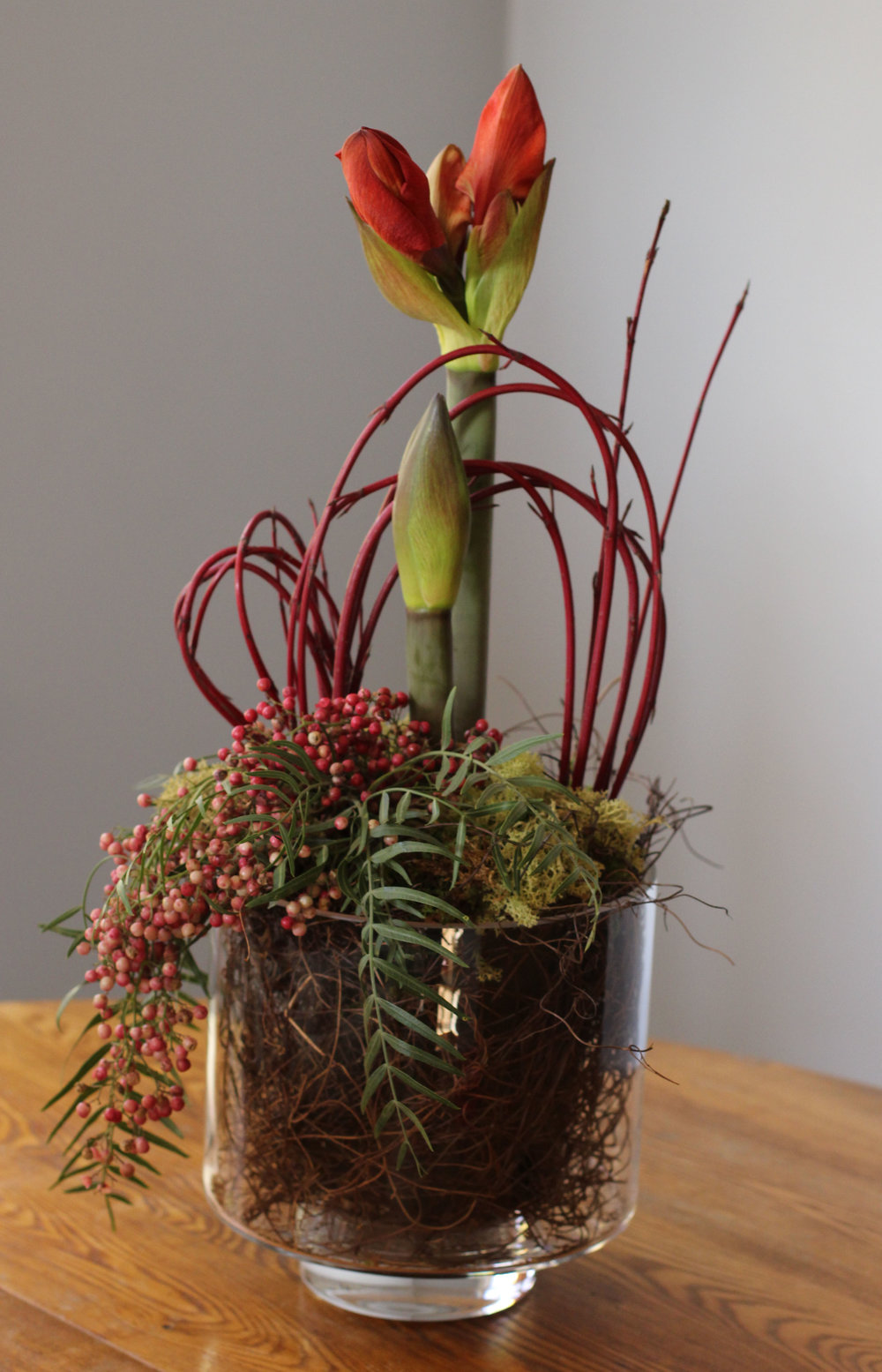 Flowering Amaryllis in footed glass vase with accents of red twig dogwood and pepperberry,  $90 .