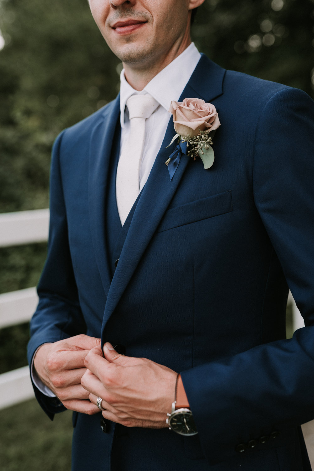 Seth is wearing a 'Amnesia' Rose Boutonniere with a backing of Eucalyptus greenery.