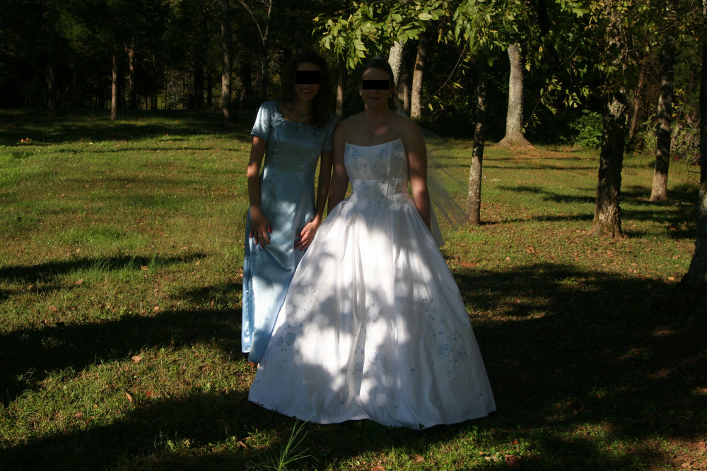 "Somewhere in that gloom of shade is the maid of honor and the bride . . . I think.  The pose on the maid of honor suggests Victorian post-mortem photography; the poor dear done died of the heat and they propped her up, bless her heart.  Bright, sunny days do present certain challenges to photographers because unlike human eyes, the camera cannot adjust easily between extremes of light and dark.  And I am willing to bet that the photographer kept his camera on ""auto"" so that it just took an average for the exposure, resulting in very dark faces.  The solution would be to use a flash and underexpose the background . . . or find a different spot.  Based on the shadows, at least one side of the church was in full shade."