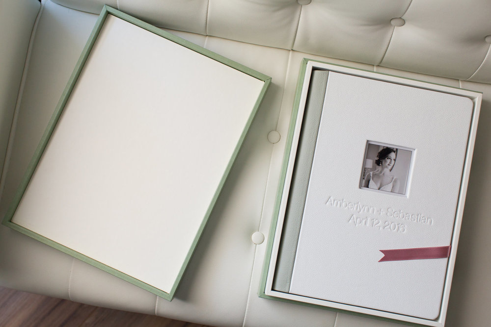 "The Original Wedding Book is shown here at 9.5"" x 13"" in a white leather with olive green leather spine and backing, die cut window with image, and embossing.  This album is kept in a Design Box covered in a sage green leatherette."