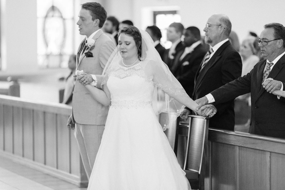 Sara holds Josh's hand, and the hands of her father and stepfather, at her wedding last summer while reciting the Our Father.
