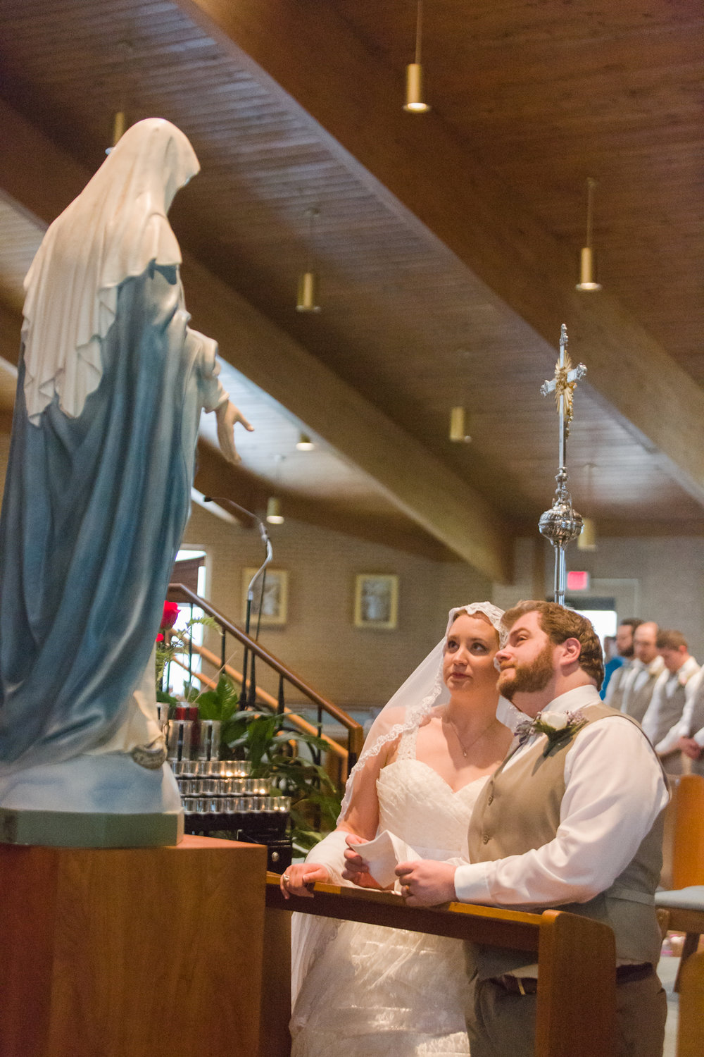 Bekah and Shea pray before the statue of Our Blessed Mother during their wedding in June.