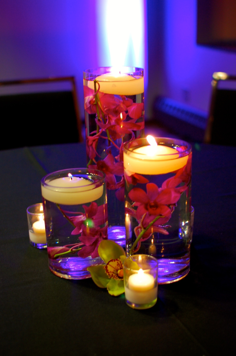 Floating candles in vases filled with purple orchids give the tables a simple and elegant look