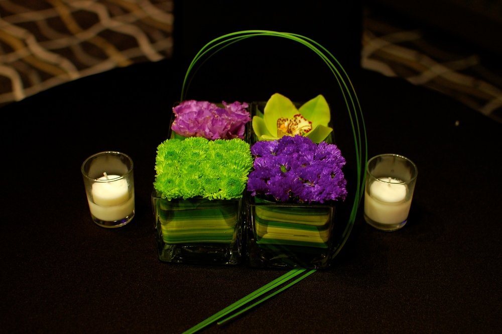 Four vases of different green and purple flowers created an interesting centerpiece tied together with some bear grass.