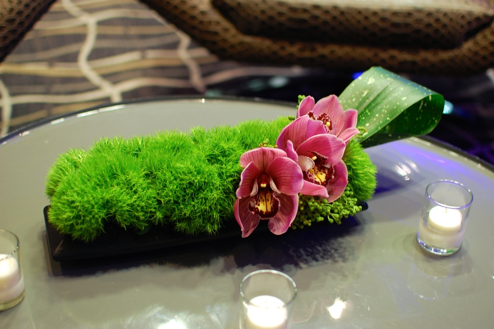Long arrangement of green dianthus and cymbidium orchids dressed up the coffee table