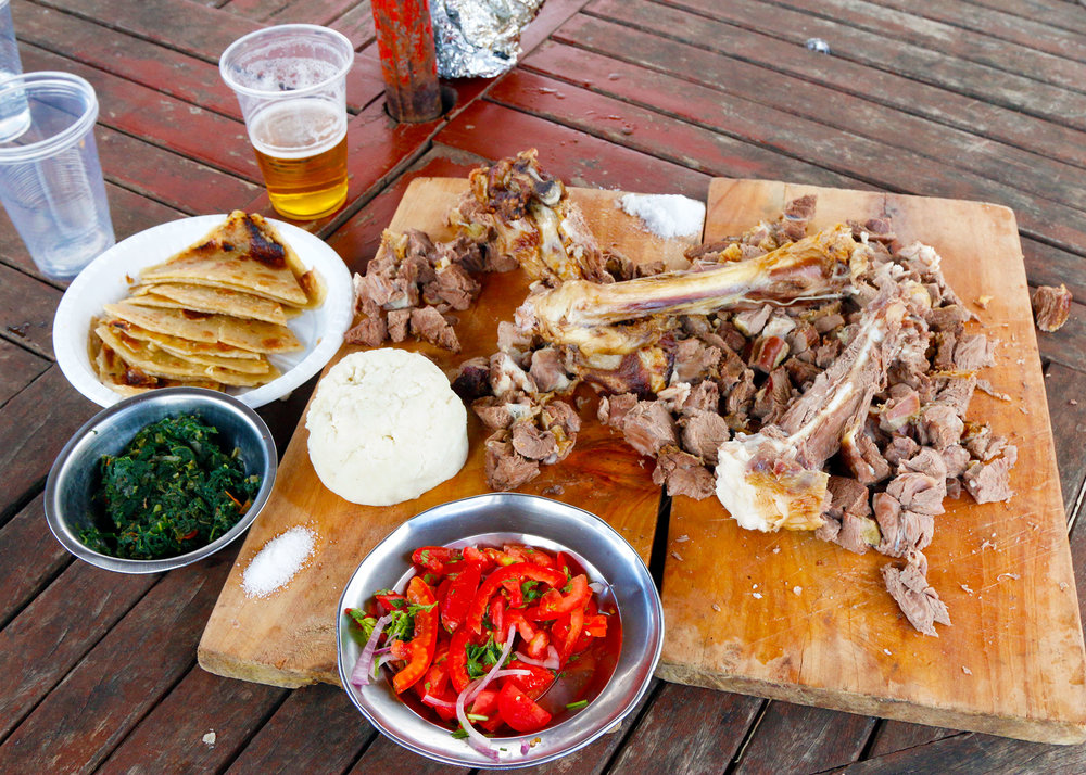 A full nyama choma spread: Sauteed greens, salsa, ugali, grilled goat leg, and, of course, cold beer.