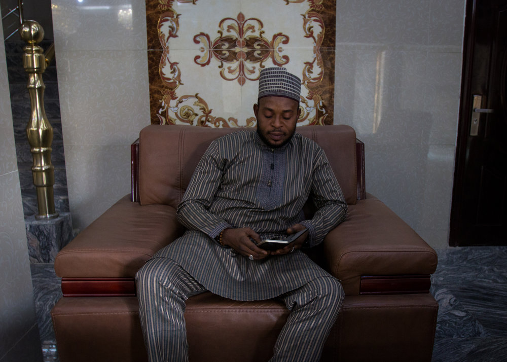 """Ambassador"" Smart Oluwadola, a cryptocurrency peddler in the city of Kano, in the hotel lobby where he often does business. (Tim McDonnell for Businessweek)"