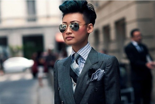 Esther Quek playing homage to English style and menswear in a regimental tie and slate tailored suit