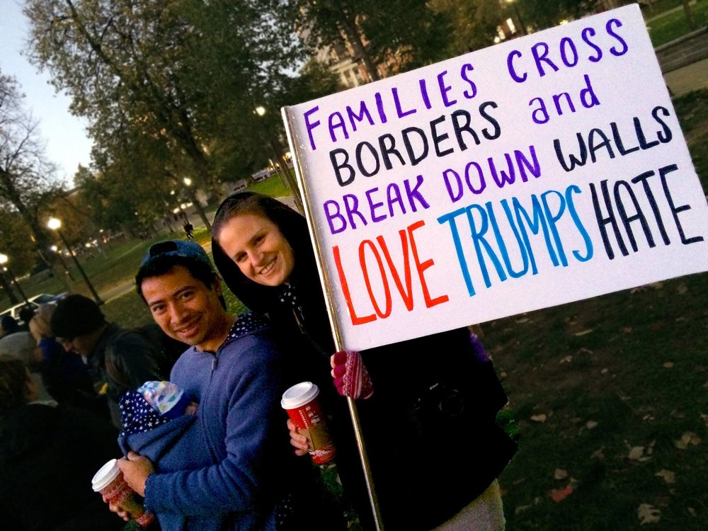"A multi-racial family at the peace rally with their newborn. ""Families Cross Borders & Break Down Walls"""