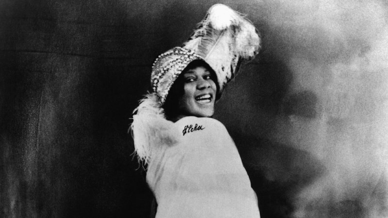 In this black and white photo, Bessie Smith, a black woman, wears an extravagant flappers hat with a huge feather on top. She wears a white shall, with her shoulder turned to the camera. She is smiling.