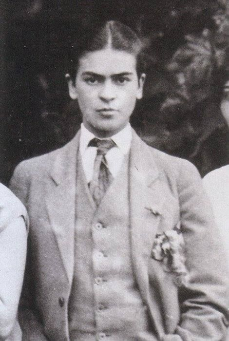 In an old black and white photograph, a young Frida Khalo stares deeply into the camera. Her hair is pulled back and parted down the middle. She is wearing a dashing 3 piece men's suit and tie.