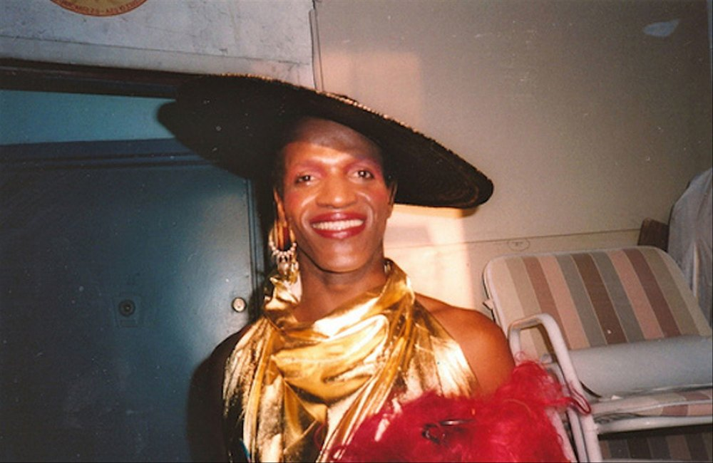 Iconic photo of Marsha P Johnson, a Black trans woman, wearing a wide rimmed hat, a golden fabric wrapped around their neck, and a decorative hoop earring