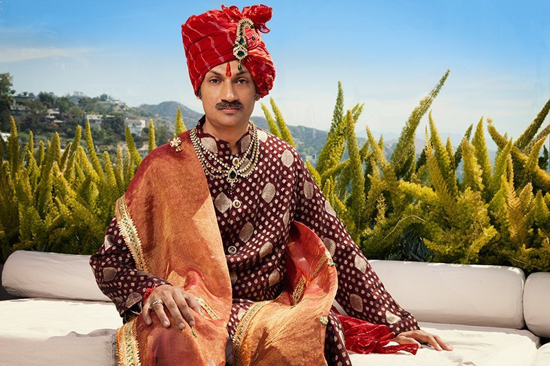 Indian man with red turban with intricate jewelry, a red  bindi running up his forehead, a mustache, a loose maroon shirt with gold detailing, and a red-orange shall with gold details. He has a beautiful golden necklace with a large tree stone in the middle.