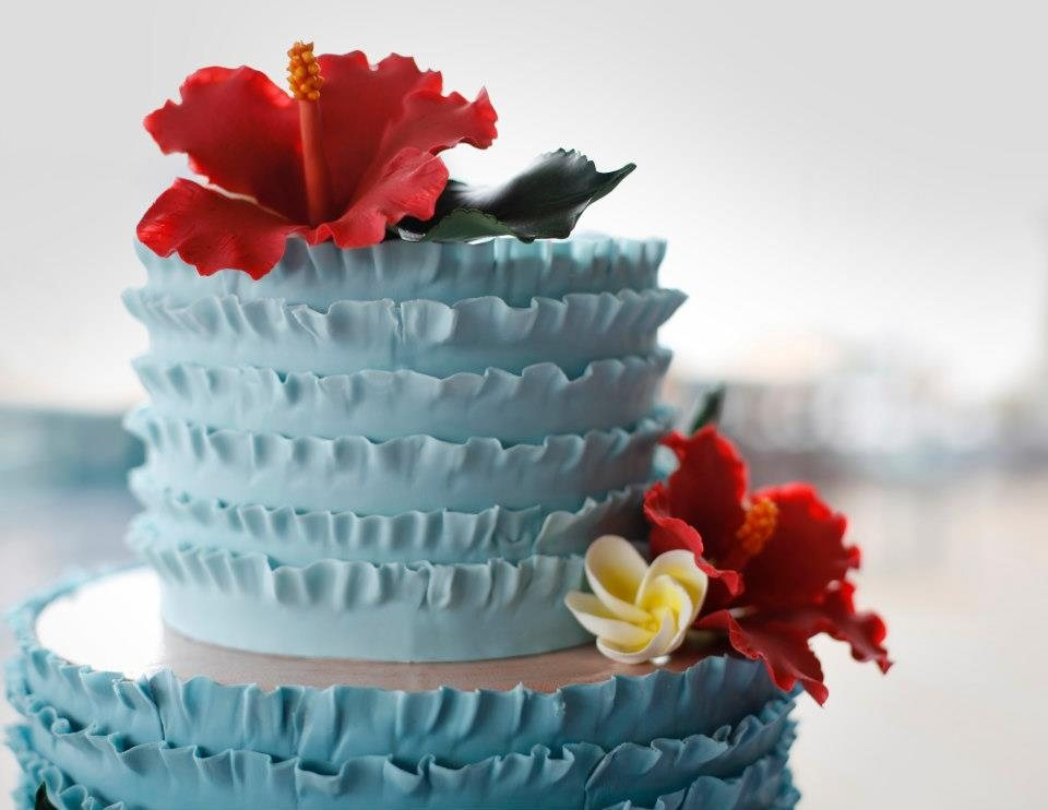 Sugar Hibiscus, Plumerias, and Hibiscus Foliage on a ruffled cake. Image © Carla Schier.