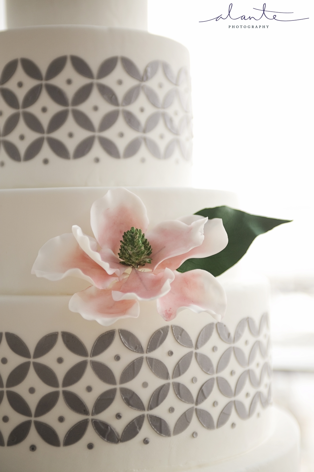 Sugar Magnolia and leaf on a geometric grey-and-white cake. Image courtesy of Alante Photography.