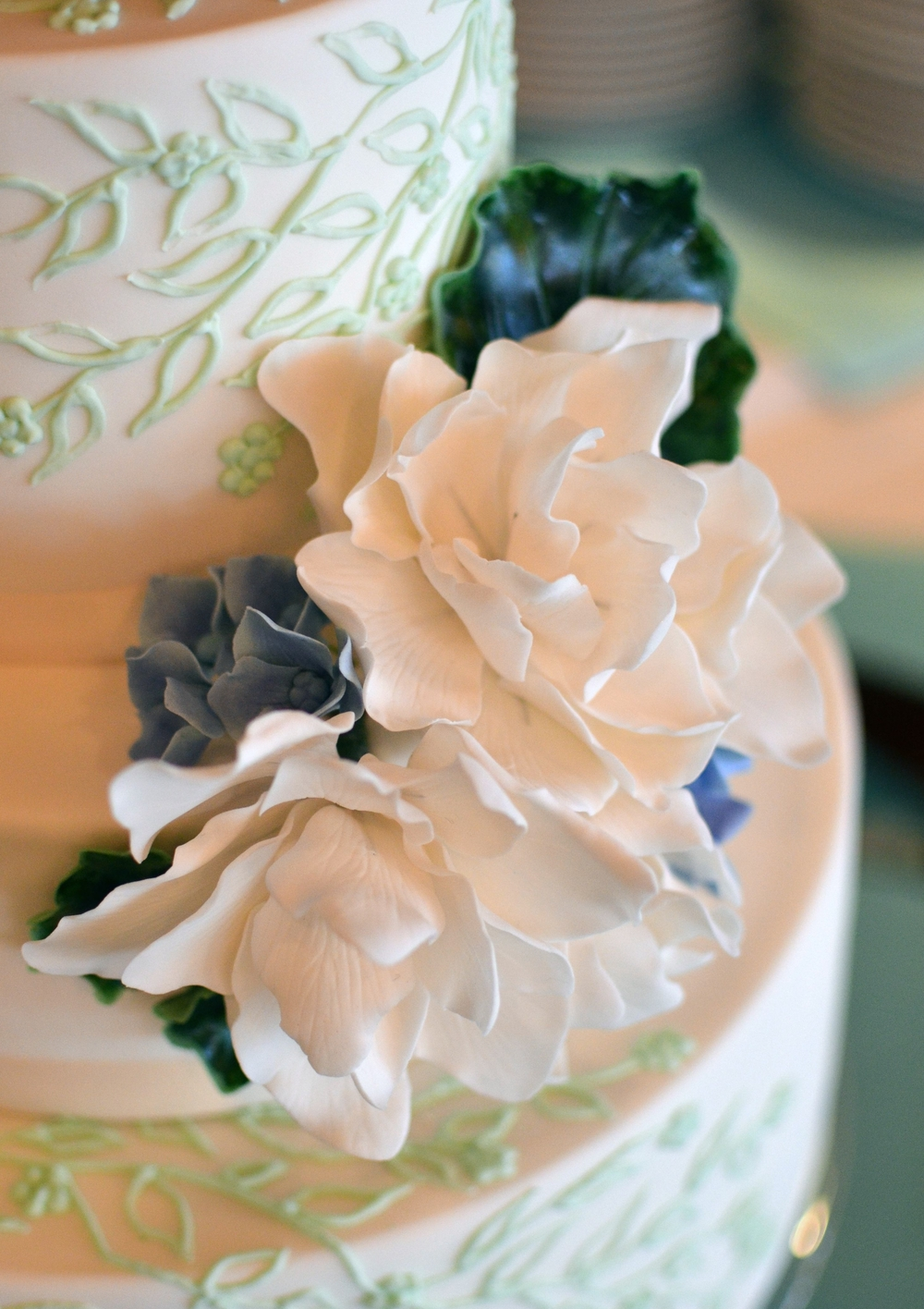 Sugar Gardenias, Hydrangeas, and Variegated Geranium Leaves on a delicate Mint Green and Ivory Wedding Cake. Image © Carla Schier.