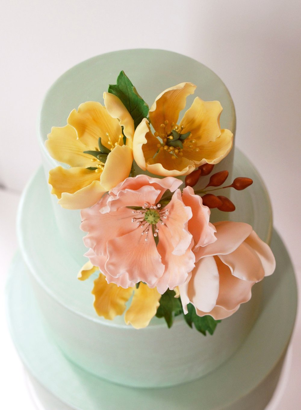 Soft pastel sugar blooms on a pearlized mint-green cake. Image © Carla Schier.