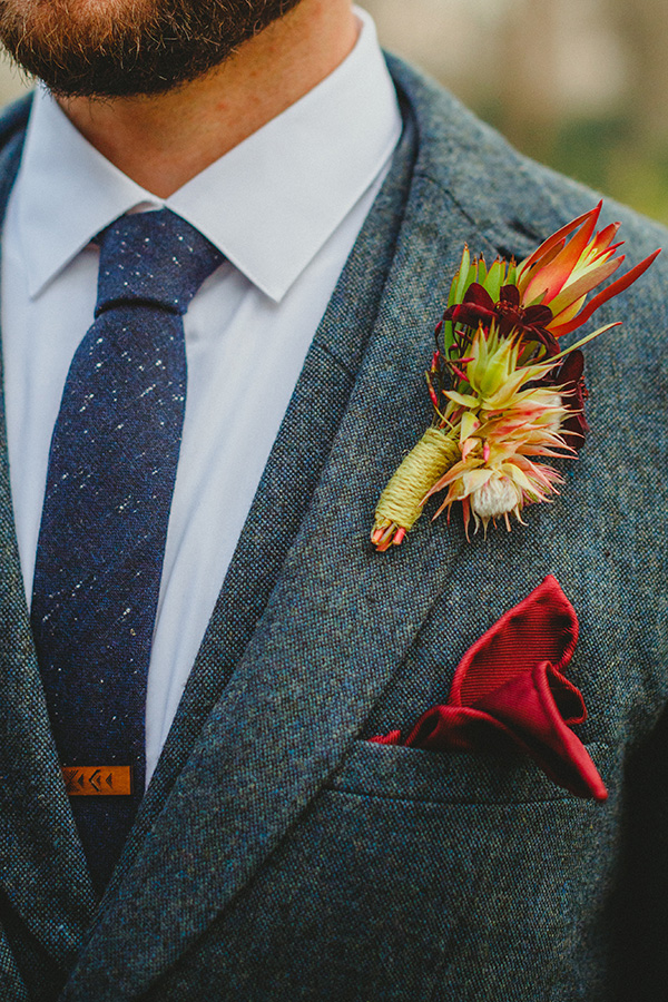 TK's boutonniere included blushing bride protea, chocolate cosmos, and safari sunset for a masculine yet romantic appeal.