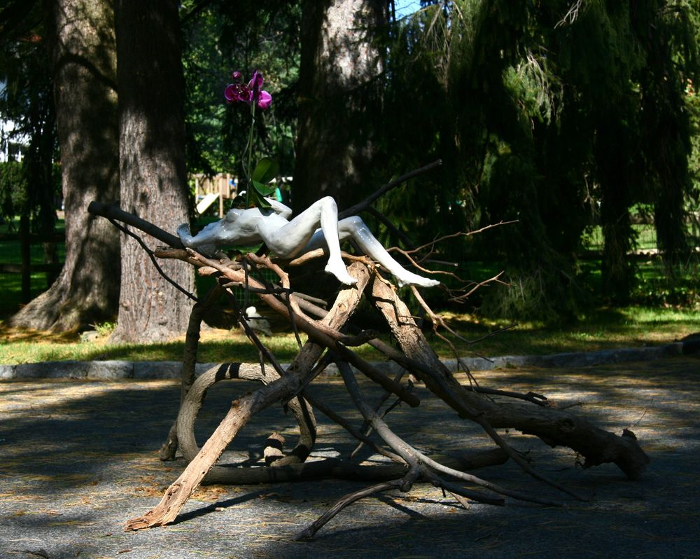 "Woman with Orchid, on branches, installation view,  5'x6'x40""H, raku-fired stoneware, branches, orchid"
