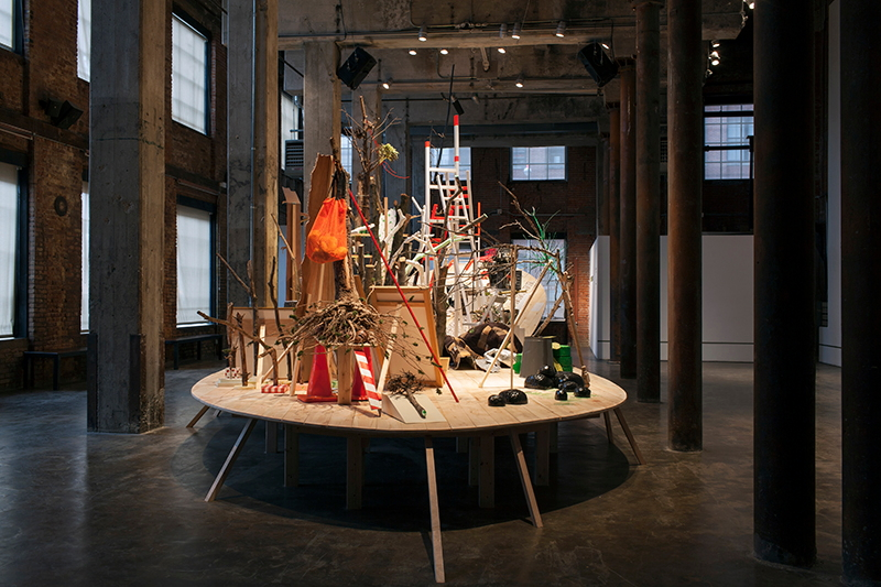 Andrea Loefke,  Homecoming  at Smack Mellon, Brooklyn, 2013.  Found tree branches and stumps, wood, ladders, chicken wire, traffic cones, photographs, plaster casts of tree branches, hardware, glitter pigmented latex, pedestals, milk crates, mirrors, carpet, clamps, foam, mixed media, and painted water level on walls