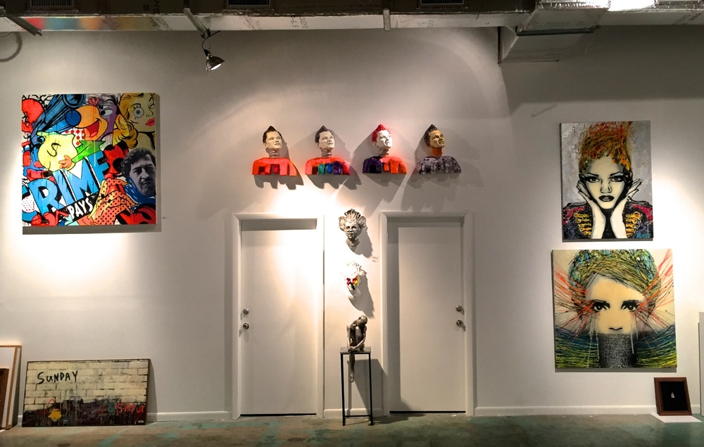 Wall-mounted head sculpture installation, contemporary figurative sculpture mask head sculpture multiples installed in Wynwood Miami at Port of Angels, a pop-up installation during Art Basel Miami 2015.     Wall-art inspired works by Timmy Sneaks on left and BLikeMe on right.