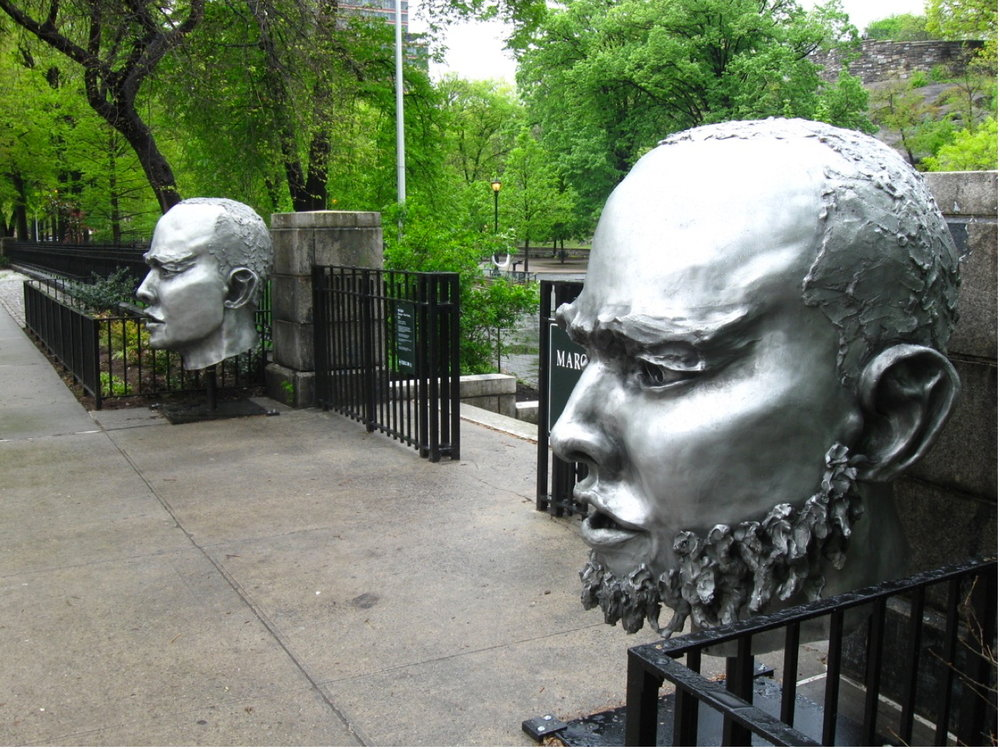 (E)scape New faces public art Head sculptures installed outdoors at Marcus Garvey Park, Harlem NYC.  Photo Courtesy Hyperallergic.  They engage the community in a dialog with art, an aspect of art social practice outreach art in a community of color.  This is inspired by the work of such artists as Theaster Gates and Nick Cave.