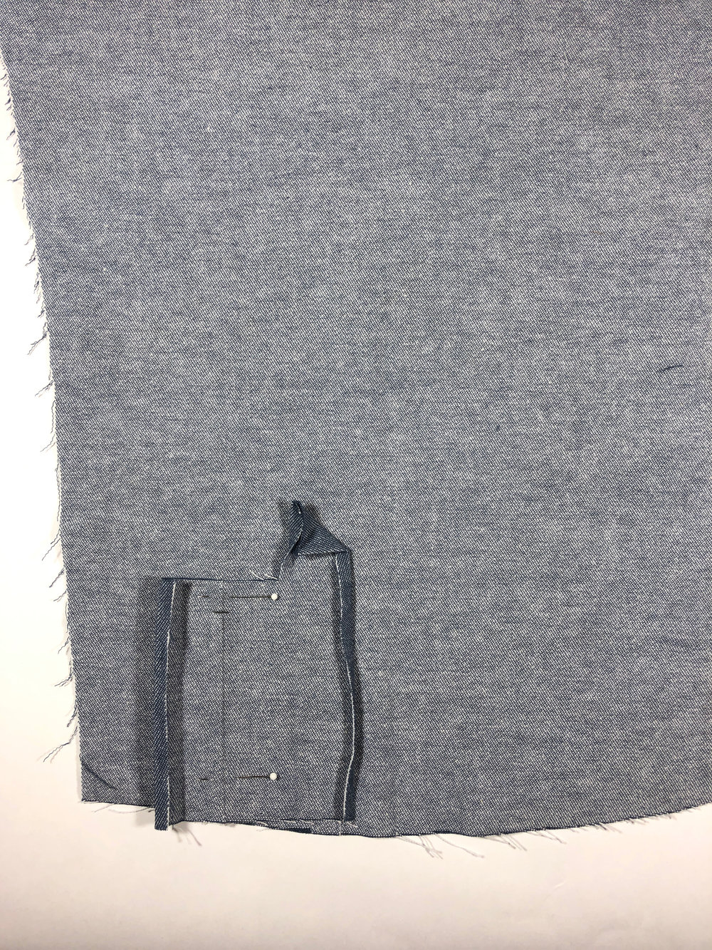 46. Unfold everything and place the placket on the WRONG side of the left sleeve. (Both placket and sleeve will be WRONG side up at this stage.)  Line the cutting line up with the left most notch on the sleeve, and pin into place. Keep the marked cutting line parallel with the sleeve grain line, by aligning the notch mark on the placket to the dot mark on the sleeve.