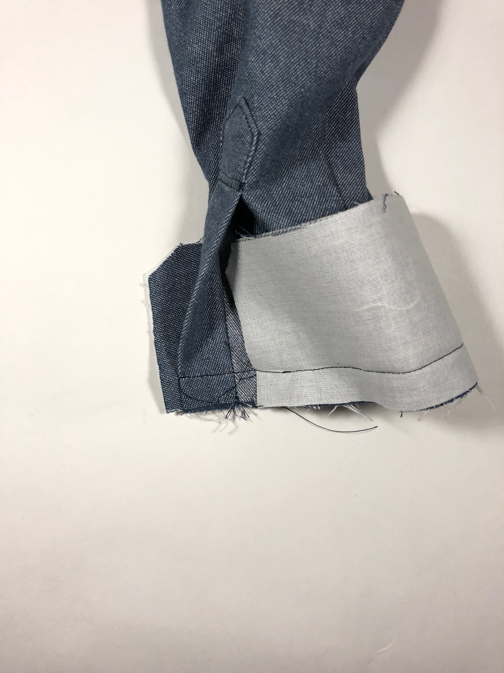 "65. With right sides together, stitch the interfaced cuff to the sleeve hem with a 5/8"" seam allowance. The cuff should extend past the placket openings by 1/4""."