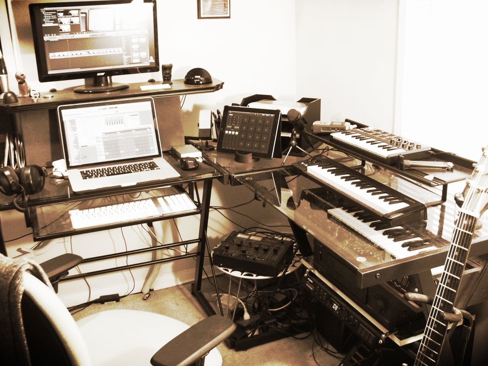 "My desktop studio.  Macbook Pro, iPad, Akai MPK mini laptop production keyboard, Korg micro-key keyboard controller, MiniKorg-700S analog synthesizer, Vantage ""The Ghost"" electric guitar, Alesis MicroVerb 4 effects processor, analog mixing board."