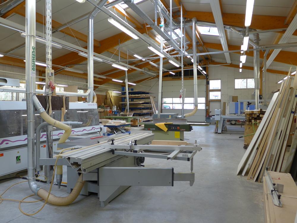 Unsere weitläufige Produktionshalle ist mit modernsten Maschinen ausgestattet. Zum Maschinenpark gehören unter anderem eine NC-gesteuerte Plattensäge, ein CNC-Bearbeitungszentrum, eine Kantenanleimmaschine und eine Vakuumpresse für Formverleimungen.